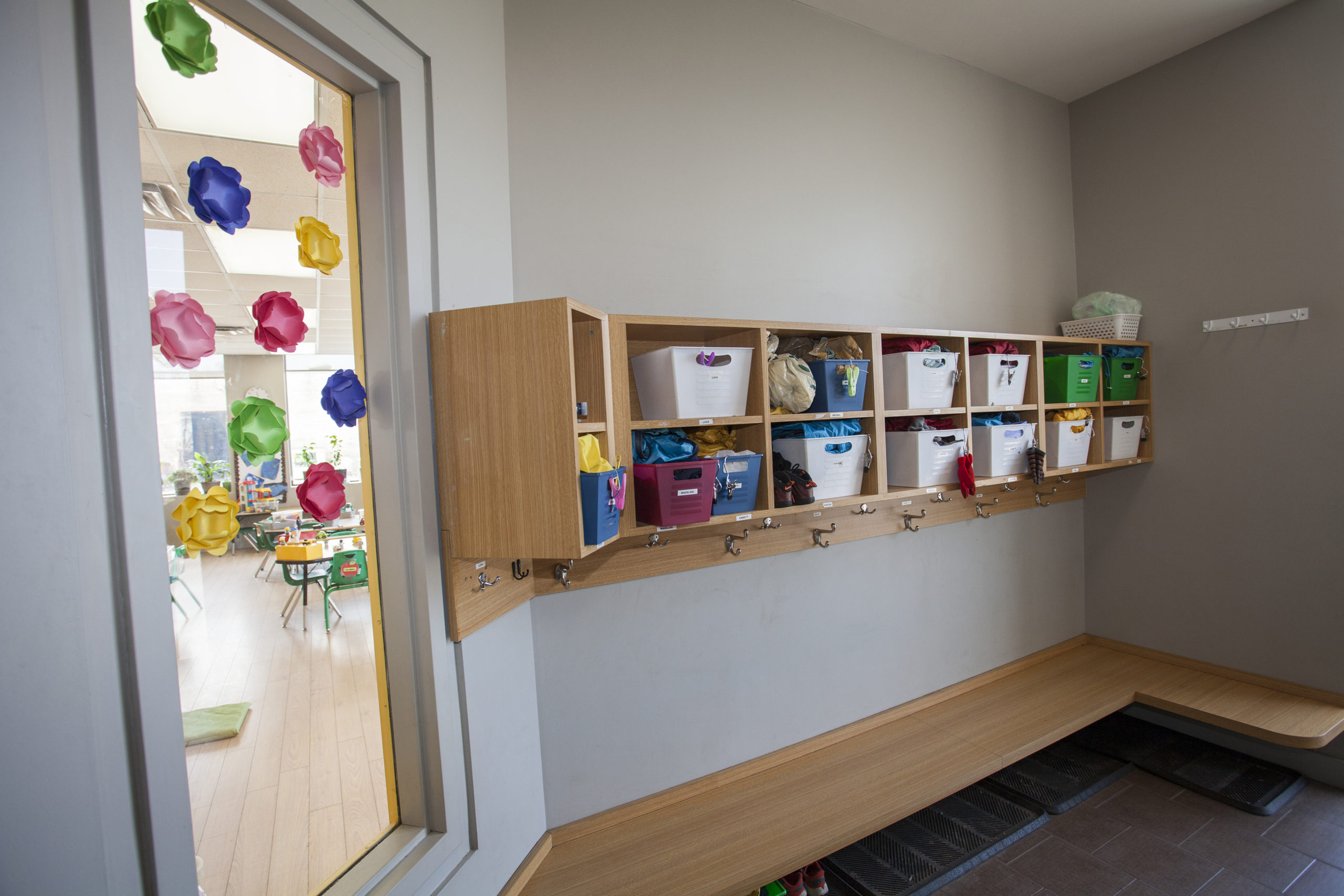 cubby area with coat hooks and bins